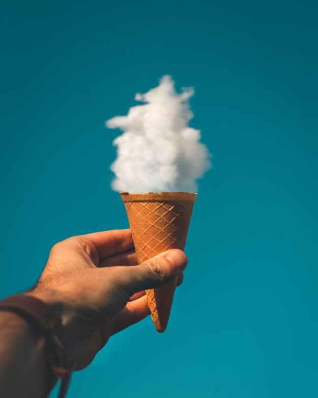 man holding ice cream cone under cloud